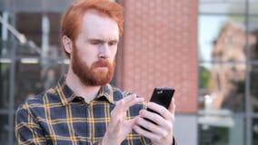 Giovane della barba all'aperto della testarossa facendo uso di Smartphone video d archivio
