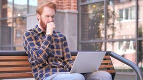 Giovane della barba della testarossa che tossisce mentre lavorando al computer portatile all'aperto archivi video