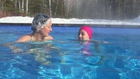 Giovane della madre nuoto della figlia insieme nello stagno termico sulla località di soggiorno di inverno archivi video