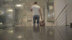 Giovane in della maglietta scale bianche giù nell'hotel video d archivio