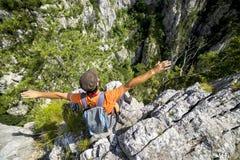 Giovane della viandante che allunga le sue armi sulla montagna Fotografie Stock Libere da Diritti