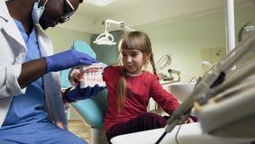 Giovane dentista africano che tiene i denti di plastica mentre bambina che lo spazzola stock footage