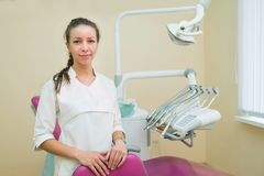 Giovane dentista femminile in ufficio dentario che sorride e che esamina macchina fotografica Fotografia Stock Libera da Diritti