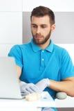 Giovane dentista maschio che lavora con il taccuino Fotografie Stock Libere da Diritti