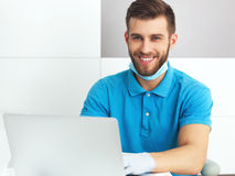 Giovane dentista maschio che lavora con il taccuino Fotografia Stock Libera da Diritti