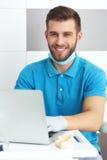 Giovane dentista maschio che lavora con il taccuino Fotografie Stock