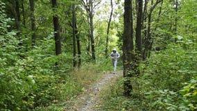 Giovane di funzionamento in foresta verde archivi video