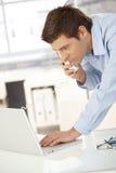 Giovane di impiegato sul telefono per mezzo del calcolatore Immagine Stock