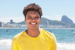 Giovane di risata da Rio in una camicia gialla a Copacabana Fotografia Stock Libera da Diritti