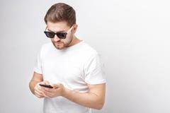 Giovane di Smilling con la barba nello sguardo degli occhiali da sole e della maglietta Fotografia Stock Libera da Diritti