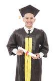 Giovane diploma e sorridere della tenuta dell'uomo di graduazione Fotografie Stock Libere da Diritti