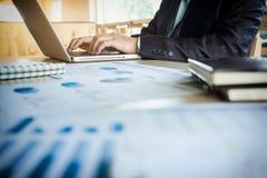 Giovane direttore aziendale che lavora all'ufficio con il computer portatile e il financi immagine stock libera da diritti