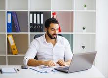 Giovane direttore moderno bello allegro che lavora ad un computer portatile nella h fotografie stock libere da diritti