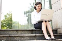Giovane dirigente femminile asiatico che per mezzo del computer portatile Fotografia Stock Libera da Diritti