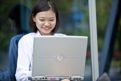 Giovane dirigente femminile asiatico che per mezzo del computer portatile Fotografia Stock