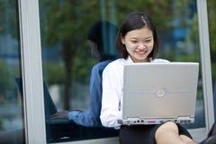 Giovane dirigente femminile asiatico che per mezzo del computer portatile Immagini Stock Libere da Diritti