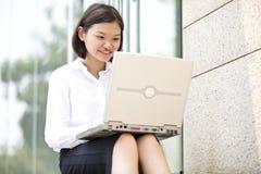 Giovane dirigente femminile asiatico che per mezzo del computer portatile Immagine Stock