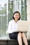 Giovane dirigente femminile asiatico che per mezzo del computer portatile Immagini Stock