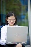 Giovane dirigente femminile asiatico che per mezzo del PC del computer portatile Fotografia Stock