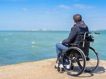 Giovane disabile che si siede in una sedia a rotelle e negli sguardi al mare immagini stock libere da diritti