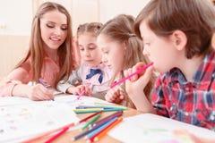 Giovane disegno dell'insegnante con gli allievi insieme fotografie stock