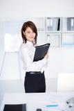Giovane dispositivo di piegatura della holding della donna di affari in ufficio Fotografie Stock Libere da Diritti