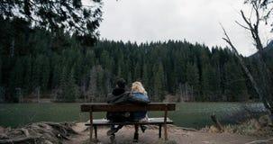 Giovane disposizione dei posti a sedere delle coppie sul banco di legno Ha esaminato il lago Guardando nell'amore tra loro video d archivio