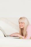 Giovane distensione femminile con un computer portatile su un sofà Immagini Stock