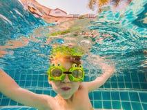 Giovane divertimento subacqueo del ragazzo nella piscina con gli occhiali di protezione Divertimento di vacanze estive immagine stock