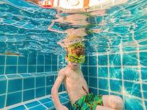 Giovane divertimento subacqueo del ragazzo nella piscina con gli occhiali di protezione Divertimento di vacanze estive fotografie stock libere da diritti