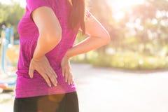 Giovane dolore asiatico di tatto della donna sul suo indietro e sull'anca mentre esercitandosi immagini stock