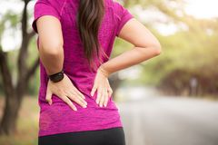 Giovane dolore asiatico di tatto della donna sul suo indietro e sull'anca mentre esercitandosi, concetto di sanit? fotografia stock