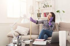 Giovane domestica che parla sul telefono durante la pulizia fotografia stock libera da diritti
