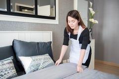 Giovane domestica che riordina letto nella camera di albergo, concetto di pulizia di servizio Fotografie Stock