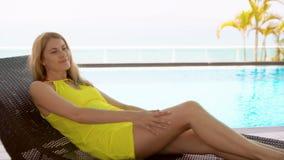 Giovane donna abbastanza vaga in vestito giallo che si trova sul lettino vicino alla piscina dell'acqua del turchese archivi video