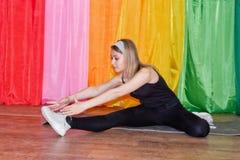 Giovane donna in abbigliamento di sport che si esercita su relativo alla ginnastica Immagine Stock Libera da Diritti