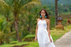 Giovane donna abbronzata in vestito bianco che posa condizione sulla strada Nei precedenti sono le palme e l'altra vegetazione tr immagini stock