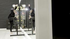 Giovane donna in abiti sportivi che fanno allungamento nella palestra davanti allo specchio azione Impacciato - guardare fare del archivi video