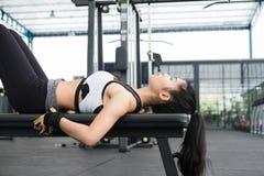 Giovane donna in abiti sportivi che fanno allungando esercizio prima del treno Fotografia Stock