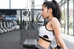 Giovane donna in abiti sportivi che fanno allungando esercizio prima del treno Fotografie Stock