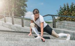 Giovane donna in abiti sportivi che fanno allungando gli esercizi all'aperto Ragazza che fa riscaldamento sui punti prima della f Fotografie Stock Libere da Diritti