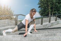 Giovane donna in abiti sportivi che fanno allungando gli esercizi all'aperto Ragazza che fa riscaldamento sui punti prima della f Immagini Stock Libere da Diritti