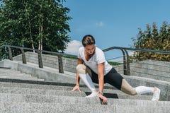 Giovane donna in abiti sportivi che fanno allungando gli esercizi all'aperto Ragazza che fa riscaldamento sui punti prima della f Immagini Stock