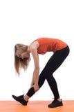 Giovane donna in abiti sportivi che si prepara indietro e gamba su una stuoia arancio Fotografia Stock