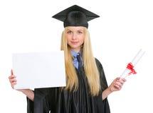 Donna in abito di graduazione che mostra tabellone per le affissioni in bianco Fotografie Stock