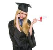 Ragazza in abito di graduazione con il telefono di conversazione del diploma Fotografia Stock