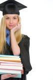 Giovane donna in abito di graduazione con la pila di libri Immagini Stock
