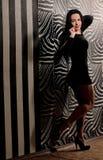 Giovane donna in abito nero all'interno immagini stock