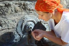 Giovane donna in acqua potabile del kerchief Fotografie Stock Libere da Diritti