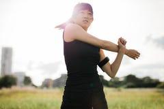 Giovane donna adatta che allunga armi al parco Immagini Stock Libere da Diritti